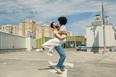 Happy young multicultural couple hugging and having fun together. On street stock photo