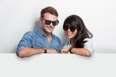 Happy Young Multiculture Couple with white blank billboard  Royalty Free Stock Photography