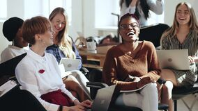 Happy young multiethnic business women sit together listening to corporate seminar laughing at modern office conference.