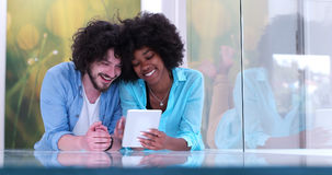 Couple relaxing together at home with tablet computer Royalty Free Stock Photos