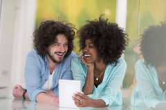 Couple relaxing together at home with tablet computer Stock Image