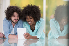 Couple relaxing together at home with tablet computer Stock Photography