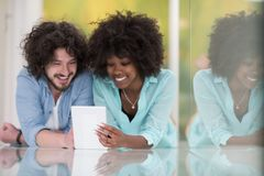 Couple relaxing together at home with tablet computer. Happy young multiethnic couple lying on floor having fun using Digital Tablet Stock Image