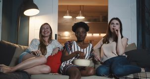 Happy young multiethnic female friends watching movies at home, smiling together expressing various emotion slow motion. stock video footage