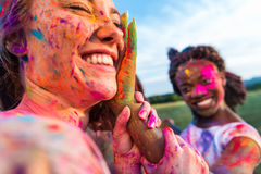 Young multiethnic friends having fun with colorful powder at holi festival of colors. Happy young multiethnic friends having fun with colorful powder at holi Royalty Free Stock Photo
