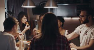 Happy young multiethnic friends having pizza and drinks, enjoying food feast and talking at house party slow motion. stock video footage
