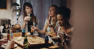 Happy young multiethnic friends, men and women sit together in the kitchen enjoying pizza and drinks party slow motion. stock video