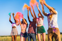 Young multiethnic friends throwing colorful powder at holi festival. Happy young multiethnic friends throwing colorful powder at holi festival Stock Images