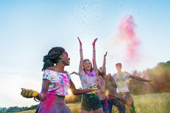 Young multiethnic friends throwing colorful powder at holi festival. Happy young multiethnic friends throwing colorful powder at holi festival Royalty Free Stock Images