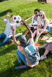 Young multiethnic students playing with soccer ball while studying in park. Happy young multiethnic students playing with soccer ball while studying in park Stock Image