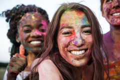 Young multiethnic women with colorful paint on clothes and bodies having fun together at holi festival. Happy young multiethnic women with colorful paint on Royalty Free Stock Photo