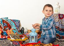 Happy young Muslim boy playing with Ramadan lantern - ready for. Iftar breakfast in Ramadan royalty free stock photography