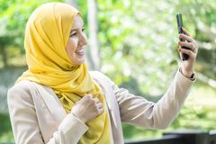 Happy young muslim woman taking selfie. Stock Photo