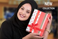 Happy young muslim woman with shopping bag and gift boxes at shopping mall. Royalty Free Stock Photos