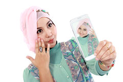 Happy young muslim woman take self portrait. With handphone Stock Image