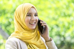 Pretty young muslim woman having a conversation on the phone. Stock Photos