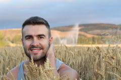 Happy young natural man relaxing on wheat summer field and smiling. Harvest concept Stock Photos