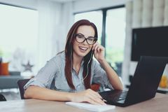 Happy young nerd woman learning to exams indoors stock photography