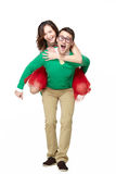 Happy young nerds couple. Piggybacking girl on her weird boyfriend isolated on white backgorund stock images
