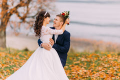 Happy young newlywed bridal couple posing on autumn lakeshore full of orange leaves Royalty Free Stock Images
