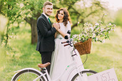 Happy young newlywed couple posing in park with bicycle Stock Images