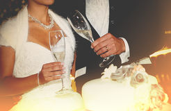 Happy young newlywed couple toasting champagne. Flutes over the cake, background lit by the lights Stock Photos