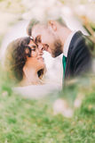 Happy young newlyweds in park. Romantic couple touching by foreheads Stock Photos