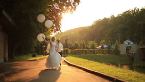 Happy young newlyweds walking with balloons in the golden autumn park on sunset and having fun together stock footage