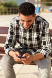 Happy young North African man looking at cellphone Stock Photography