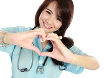 Happy young nurse with heart shape. Portrait of happy young nurse give you sign of heart shape royalty free stock photo