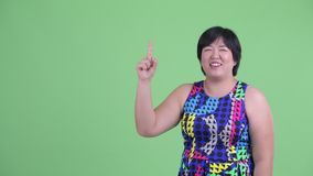 Happy young overweight Asian woman pointing up and looking surprised. Studio shot of young beautiful overweight Asian woman ready to party against chroma key stock video footage