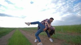 Happy young pair dancing in slow motion and enjoy vacation outdoors at countryside on background of sky. Happy young pair dancing in slow motion and enjoy stock footage