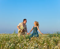 The happy young pair in the field of chamomiles Royalty Free Stock Images