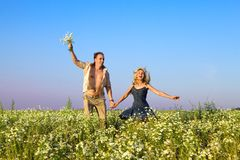 The happy young pair in the field of chamomiles ju Stock Images