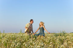 The happy young pair in the field of chamomiles jumps Stock Photo