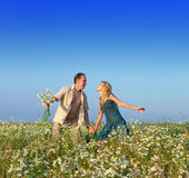 The happy young pair in the field of chamomiles Royalty Free Stock Image