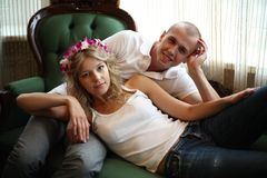 Happy young pair at home. The guy and the girl lie on a magnificent green sofa royalty free stock image