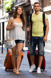 Happy young pair with luggage walking in city Royalty Free Stock Image