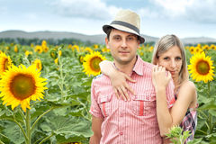 Happy young pair in sunflowers Stock Images