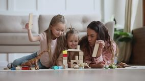 Happy mum babysitter play with children build castle of blocks