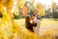 Happy young parents with baby boy in autumn park Royalty Free Stock Image