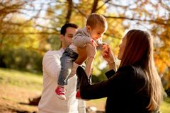Happy young parents with baby boy in autumn park royalty free stock images