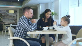 Happy young parents chatting witn daughter during their family vacation in cafe drinking tea. stock video footage