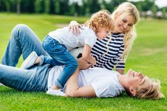 Happy young parents with cute little son holding soccer ball and having fun. At park stock photography