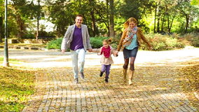 Happy young parents with daughter in park. Happy young parents with daughter running  through the park while holding each other hands stock footage