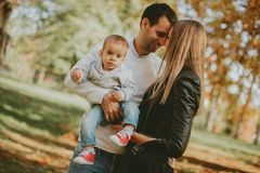 Happy young parents with baby boy in autumn park Royalty Free Stock Photos