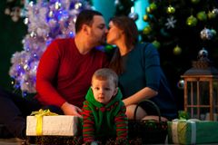 Happy young parents kiss and their little son crawls near Christ. Happy young parents kiss and their little son crawls on background of Christmas tree Royalty Free Stock Photo