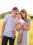Happy young parents with little child on the field royalty free stock photos