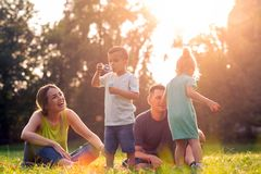 Happy parents playing with children outside stock photography