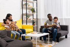 Happy young parents spending time with kids. At home Stock Image
